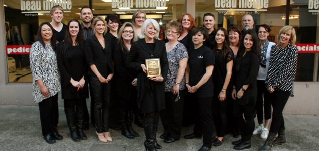 Faculty of Beau Monde posting outside the school with the Wella Professionals USA Sebastian Professional Nioxin USA School of the Year award plaque.