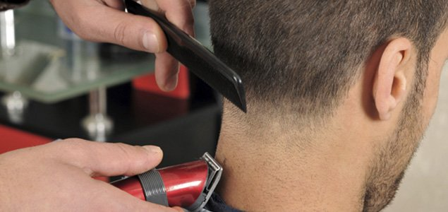 Student in the Barbering Program giving a client a haircut