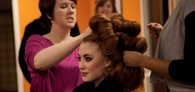 Stylists in the High School Student Program prepare a model for the runway.