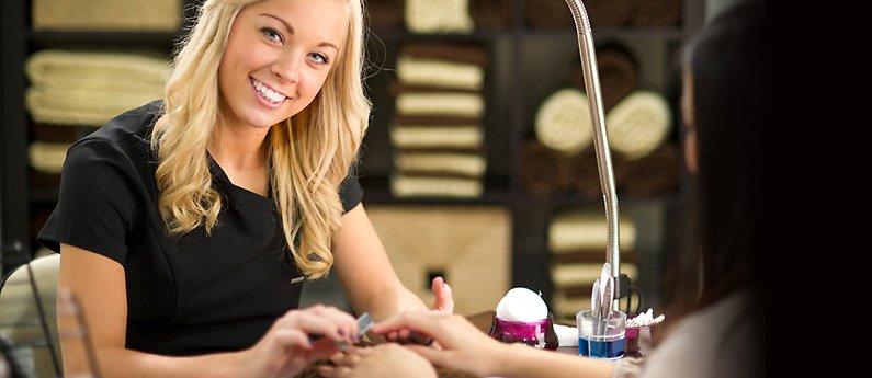 Beau Monde student giving a client a manicure