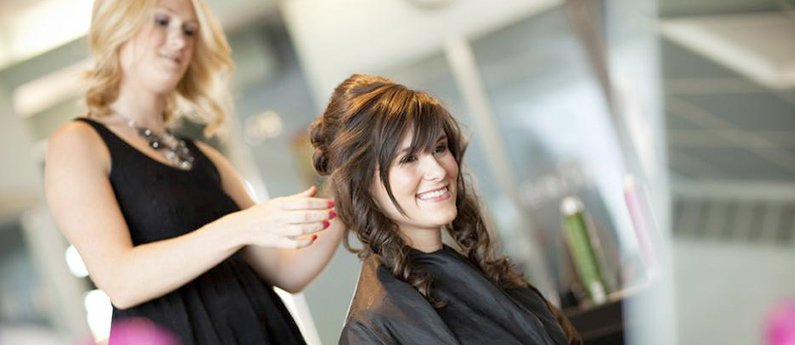 Client getting a stylish hairdo from a student at Beau Monde